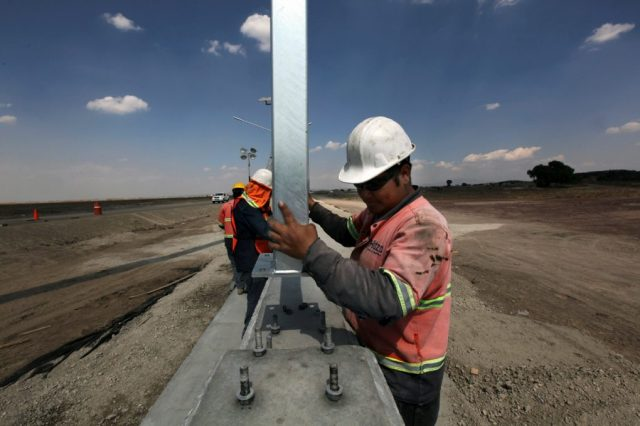 Workers install a fence for the new Mexico City international airport